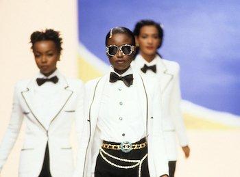 Three models walk a runway in white tuxedo jackets.
