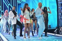 Image of models walking down a runway, preceded by singer Kelly Rowland and model Boris Kodjoe.