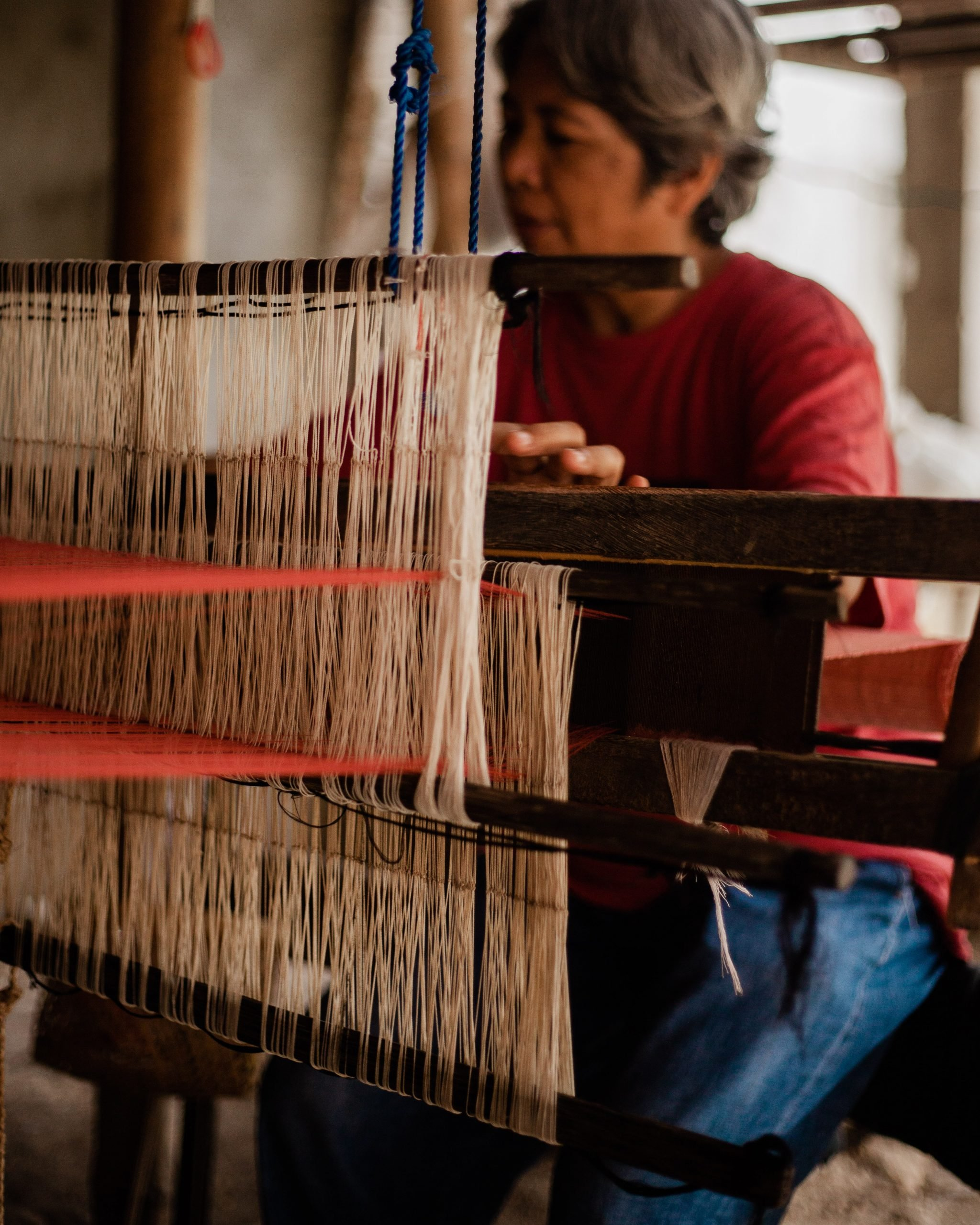 Woman in red long sleeve and blue denim jeans sitting and working on a weaving loom