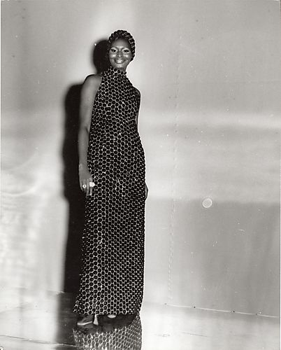 Black & white photograph. Black Model in a sleeveless sequin evening gown with matching headpiece.