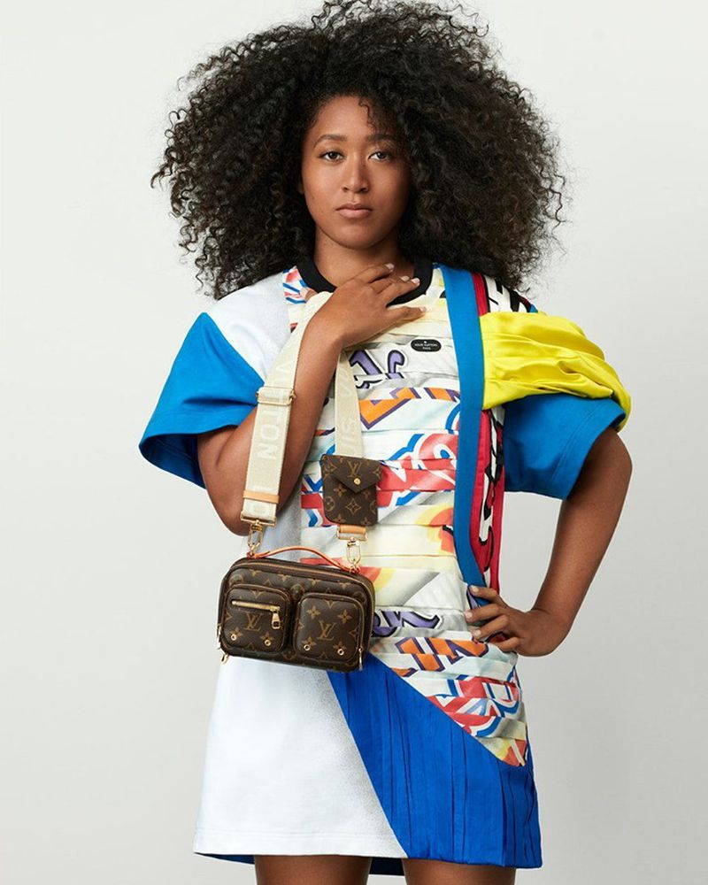 Tennis star Naomi Osaka is seen in front of a white wall, wearing garments and a handbag by Louis Vuitton