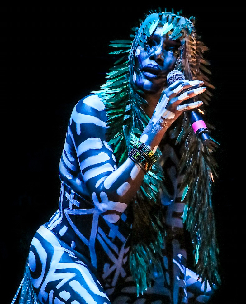 Grace Jones performing on Main Stage of 2016 FYF Festival at Exposition Park in Los Angeles, CA. She is covered in white and black body paint with tribal style white paint markings against black body paint. She is wearing a green feathered style headdress holding a microphone. Set against a black background