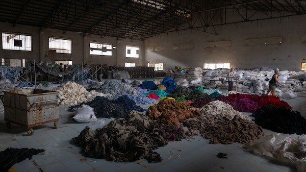 Sorting through hundreds of tons of clothing in an abandoned factory for a social mission called Clothing the Loop.