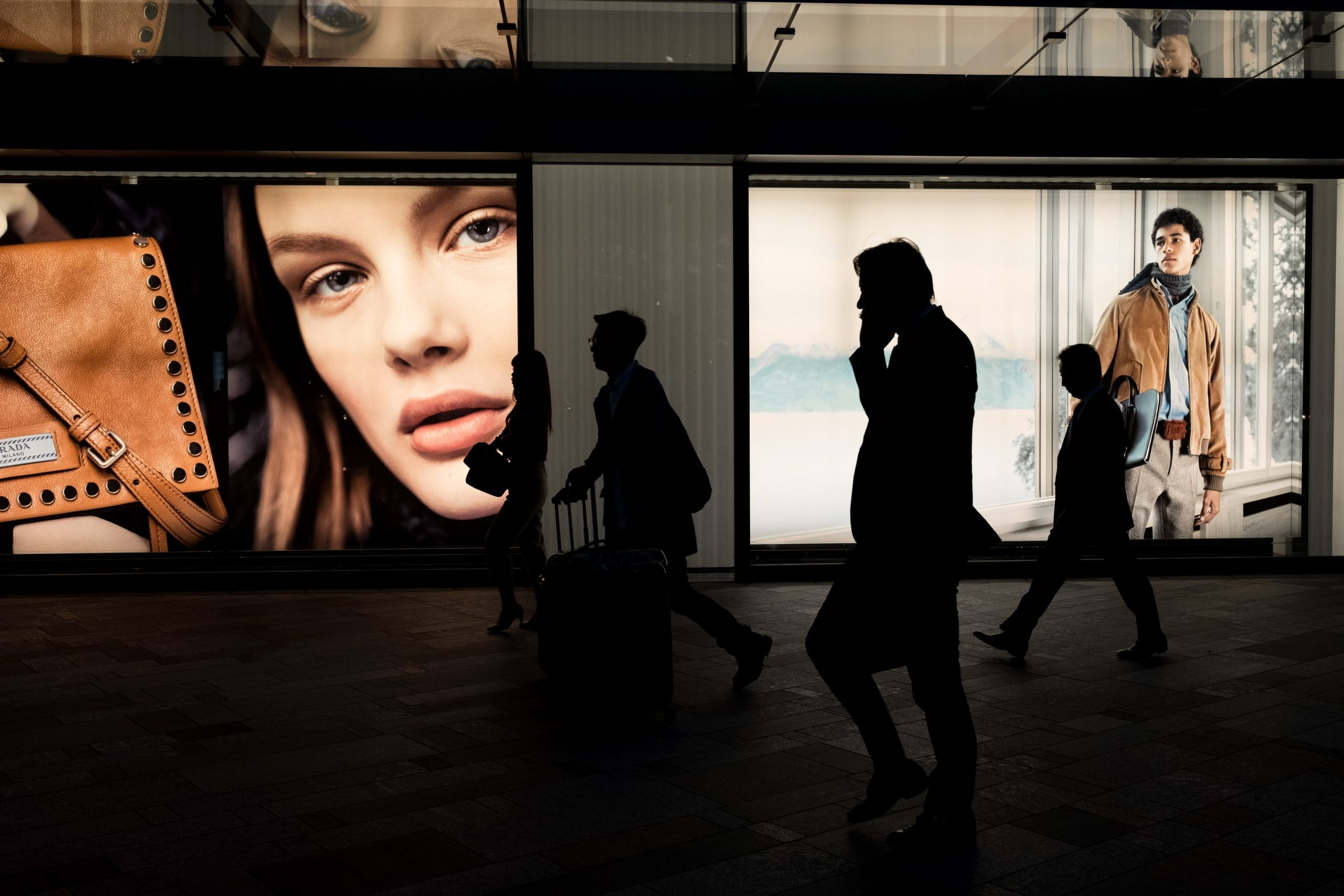 People walking in front of fashion advertisements