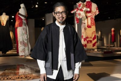 Photo of designer Akira Isogawa in front of dressed mannequins inside the gallery exhibiting his work