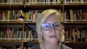 Photo of woman with short, blond hair wearing glasses and bookshelves in the background