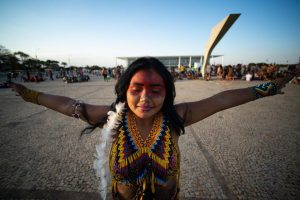 Photo of Native Brazilian woman with face paint and multi-coloured top, opening her arms to her sides