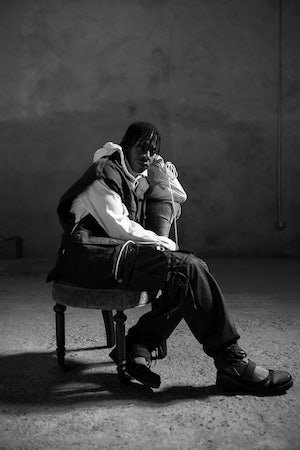 Telfar Clemens photographed seated in a black chair