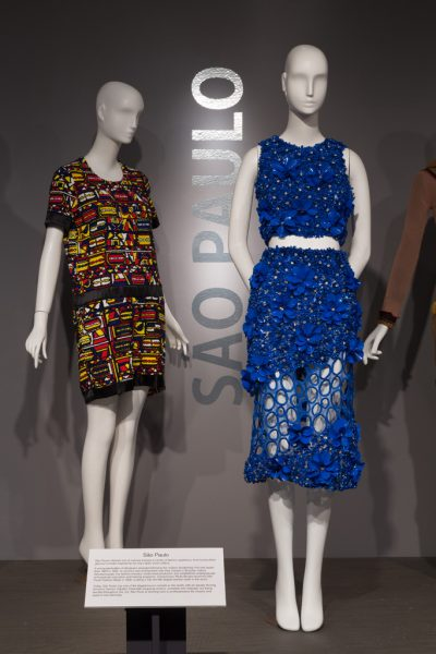 """Gallery view with two dressed mannequins and the words """"Sao Paulo"""" inscribed on the wall"""