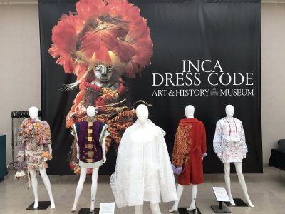 Gallery view with five mannequins with Inca-inspired dress and a banner with the title of the exhibition in the background