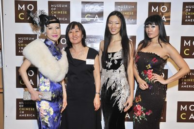 Photo of four women, one of them wearing a cheongsam, in front of a wall with the logo of MoCA, Museum of Chinese in America
