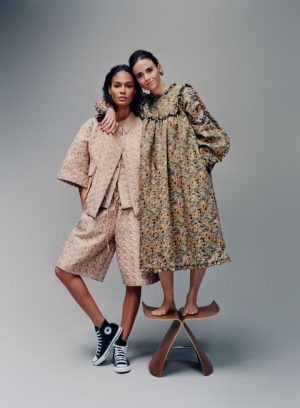 Photo of Colombian fashion designer Kika Vargas standing on a chair, standing next to a model wearing her designs, and hugging her