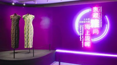 Gallery view with two mannequins dressed with cheongsams and the exhibition title in luminiscent letters