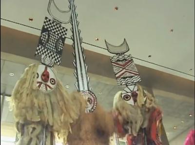 Three dancers wearing masks.