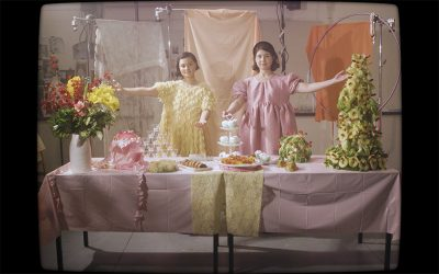 Photo of two girls wearing pastel-colored dresses behind a table with cakes and wrapped gifts