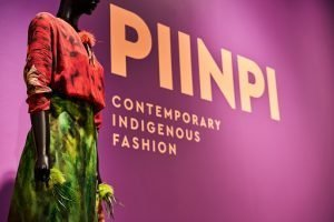 Exhibition entrance with title written in yellow letters on a purple ground and a mannequin dressed with a hot pink jacket and green skirt