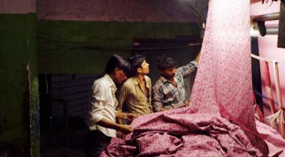 Three men looking at pink textile fabric