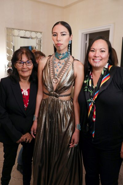 Photo of model Qhannah Chasinghorse in her Met Gala outfit, consisting of a golden dress and layered, beaded necklaces and jewelry, with two women standing by her sides
