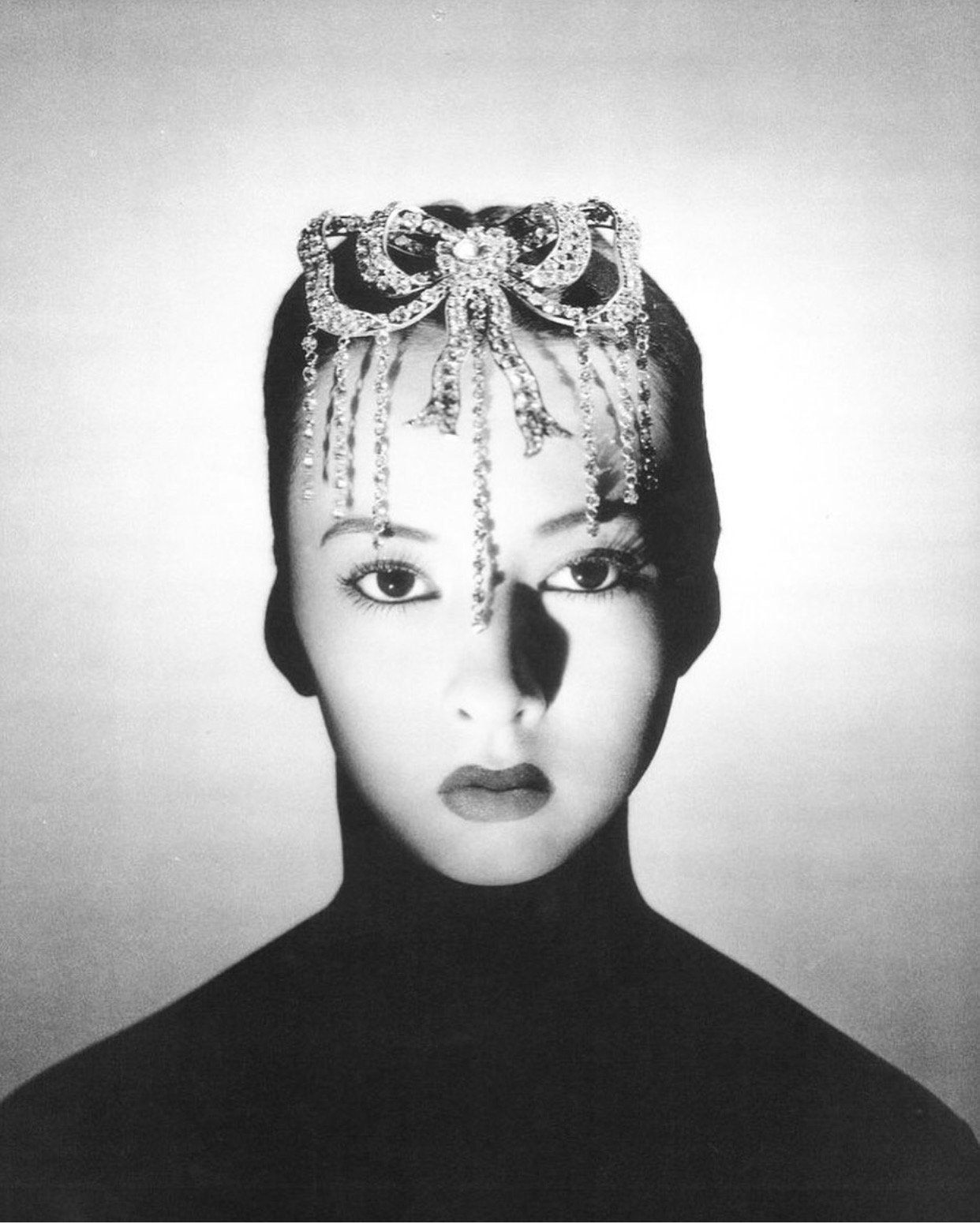 Black and white photo of actress Sono Osato wearing a Chanel jewelry headpiec in the shape of a bow and diamonds dangling down her face