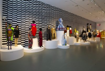 Exhibition gallery view with dressed mannequins on cylindrical platforms of different heights, lined up in front of a black-and-white wall