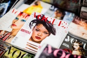 A stack of magazines is seen, an issue of Vogue with Rihanna on the cover is central