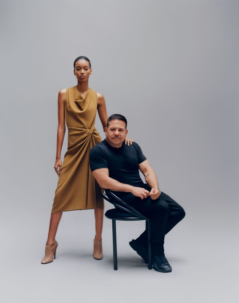 Model Manuela Sanchez standing in tan Narciso Rodriguez dress and booties. Designer Narciso Rodriguez, seated, in his own black clothes.