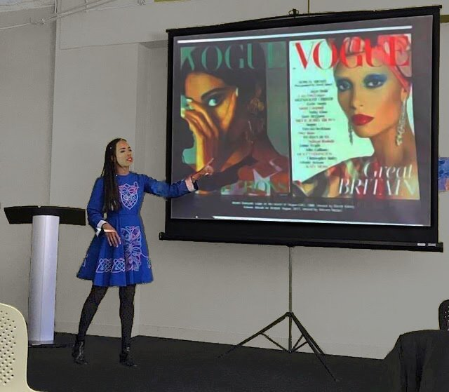 Kim Jenkins stands pointing in front of a projection screen which is showing two covers of Vogue magazine