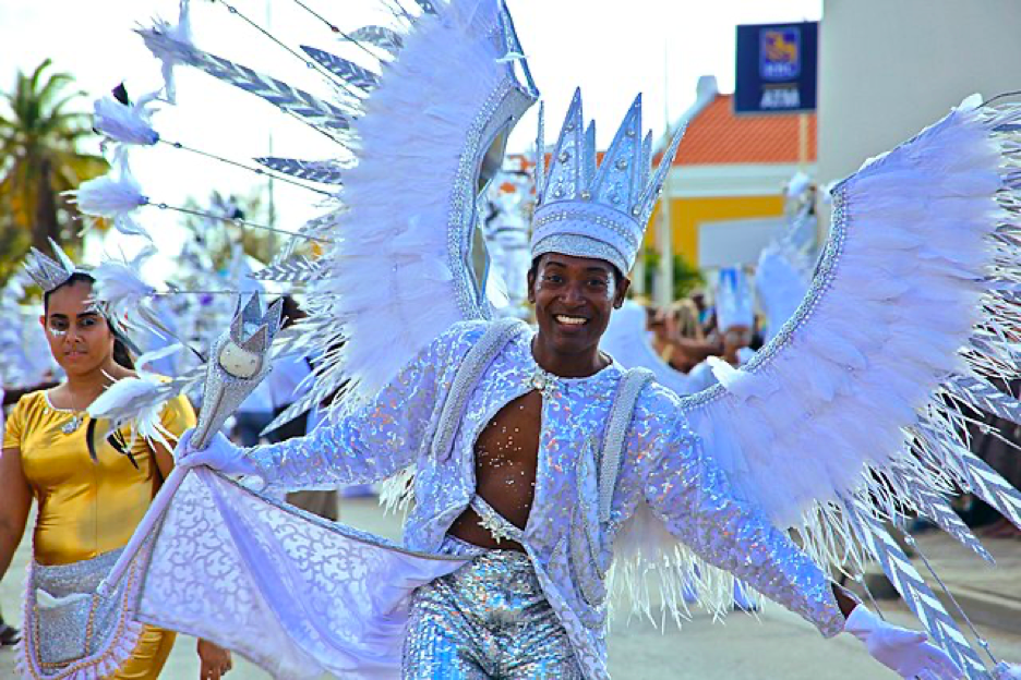 Man dressed in all white Carnivale outfit: white feathered wing harness, white bejeweled crown, white/silver sequin top and pants, and white gloves holding a bejeweled white scepter
