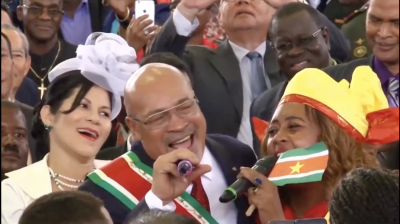 People singing, while also Suriname national flag.