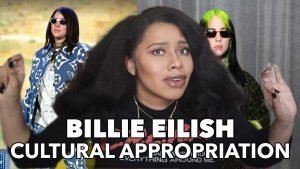 """Still from video with host in the center and two images of Billie Eilish in the background and the words """"Billie Eilish Cultural Appropriation"""" inscribed on the lower edge"""