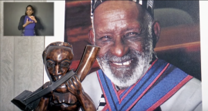To the left a woman interprets conversation. To the middle is a statue. To the right is a photograph of James Barnor