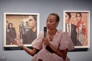 Photographer Nadine Ijewere in a pink dress, holding a microphone and standing in front of two of her photographs