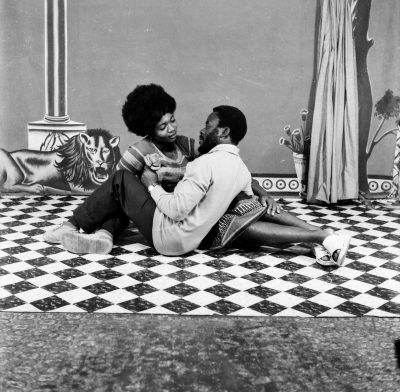 A black and white photo of a couple sitting down looking into each other