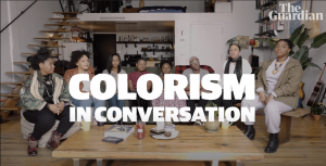 """Eight women seated in a half circle, with the words """"COLORISM IN CONVERSATION"""" in white text at the forefront"""