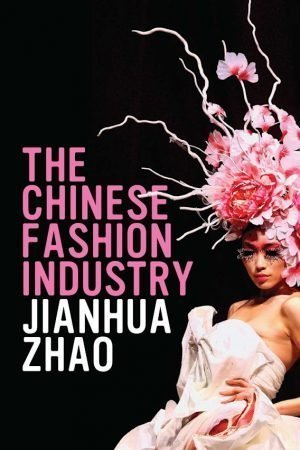 A model in a pink dress and elaborate pink, floral headpiece posing on the right half of the cover, with the text of the title in pink and the author's name in white taking up the left half.
