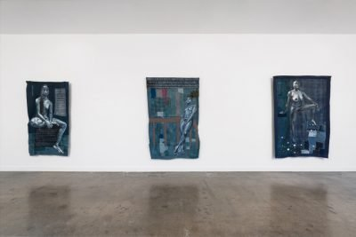 View of gallery wall with three works of art hanging