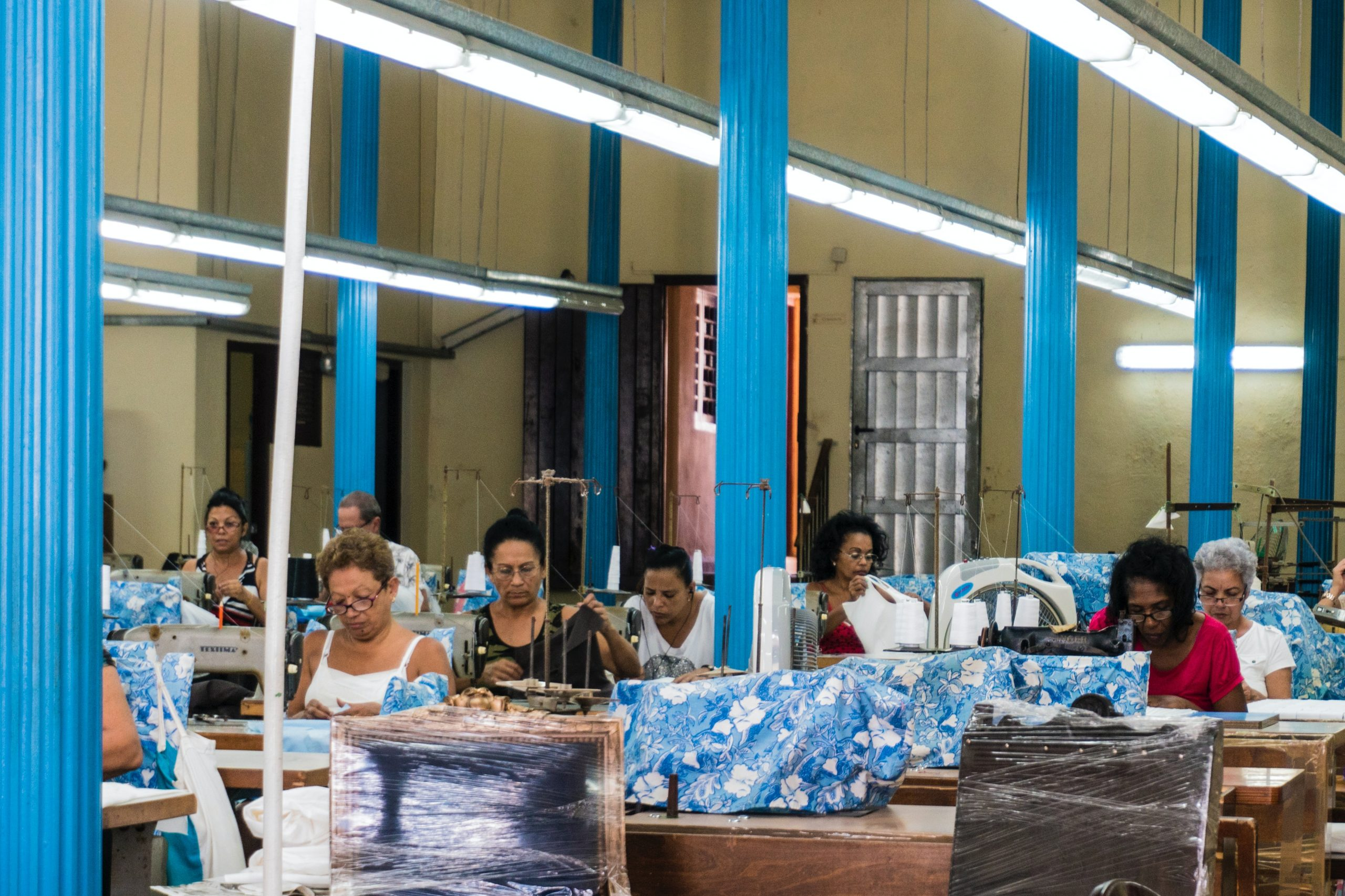 Factory workers in Havana, Cuba, are seen sitting and working at sewing machines.
