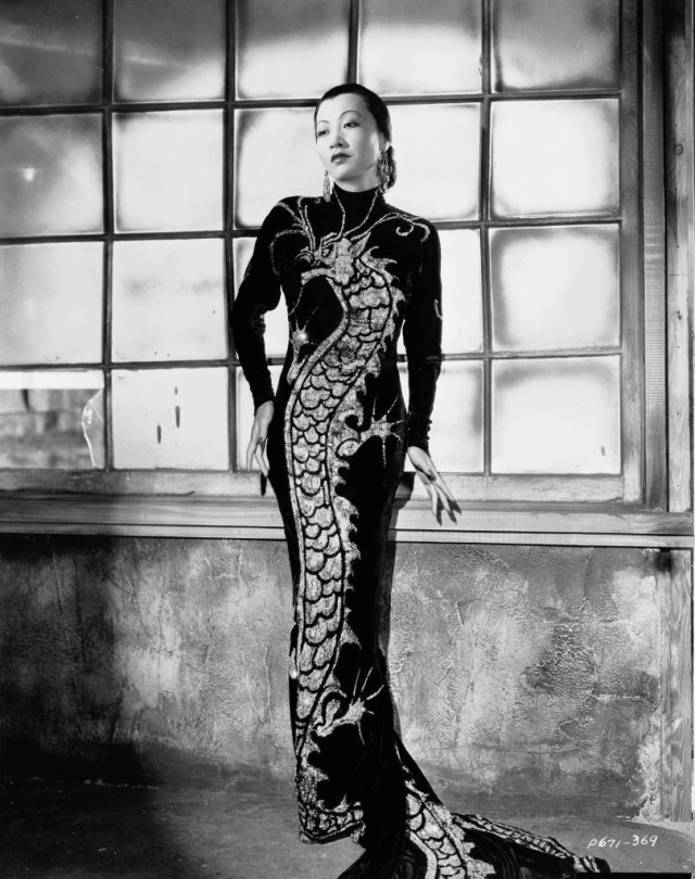 Black and white photo of Chinese-American film star, Anna May Wong (1905–61) wearing a black qipao with a dragon motif in a publicity shot for 'Limehouse Blues.,